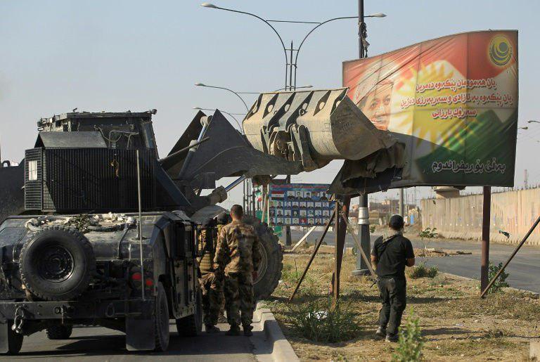 خودروی ارتش عراق در حال برداشتن تصویر مسعود بارزانی در ورودی کرکوک (عکس)