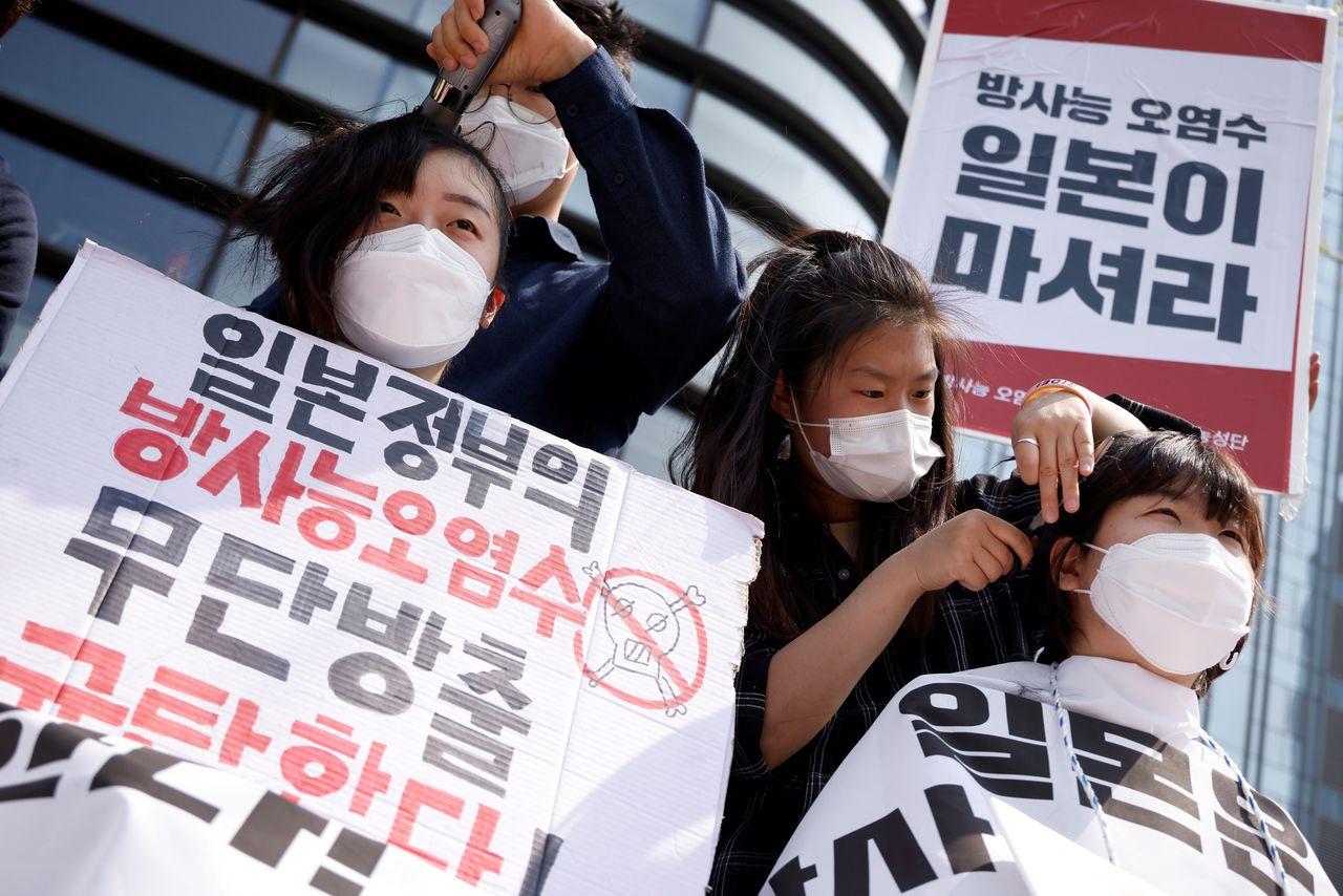 دختران کرهای در حال تراشیدن موی سر در اعتراض به ژاپن
