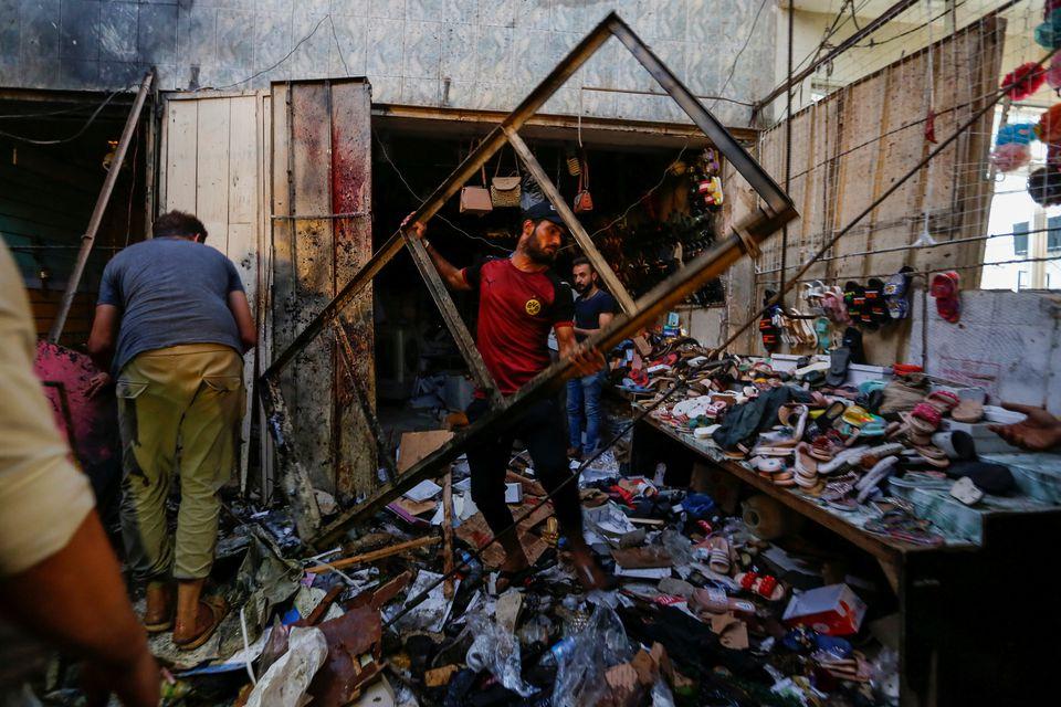 مردم در حال جابجابب بقایای انفجار بازار صدر عراق