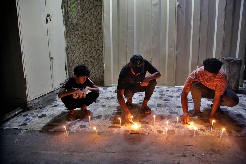 شمع روشن کردن به یاد قربانیان بازار منفجر شده بغداد