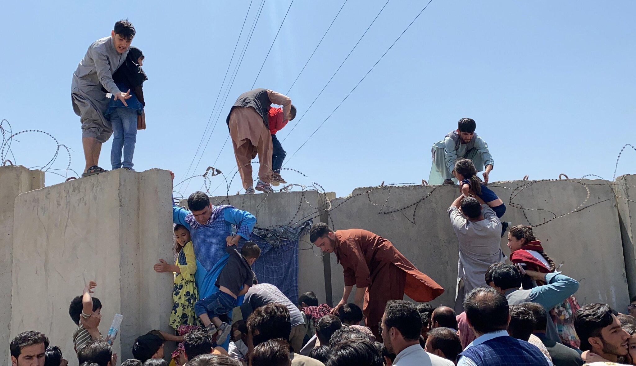 گذر مردم از دیوار فرودگاه کابل