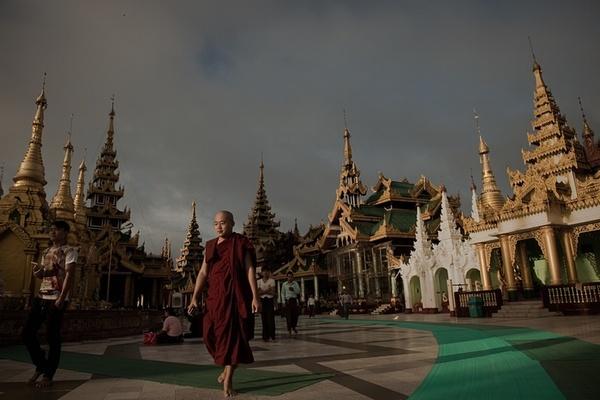راهب بودایی در حال عبور از مقابل یک معبد در شهر رانگون میانمار