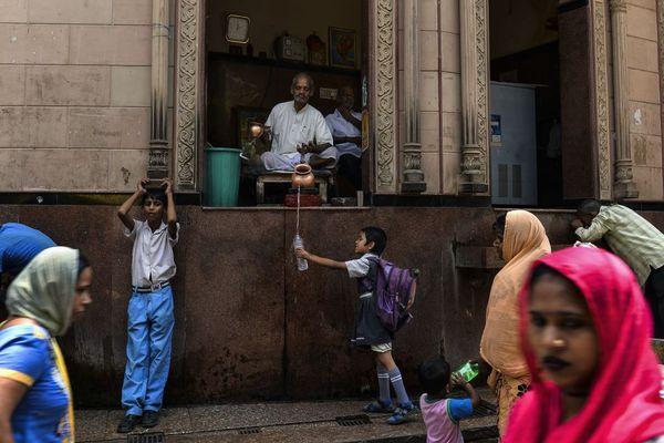 کاهن هندو در حال ریختن آب در ظرف یک کودک مدرسه ای در محله قدیمی دهلی نو