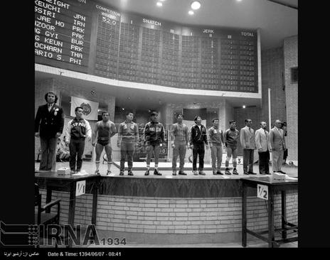سالن برگزاری مسابقات وزنه برداری بازی های آسیایی تهران و محمد نصیری قهرمان وزنه برداری ایران،نفر سوم از سمت چپ، در تصویر دیده می شود