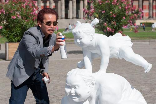 هنرمند چینی در حال کار روی مجسمه های خود در پارکی در شهر برلین