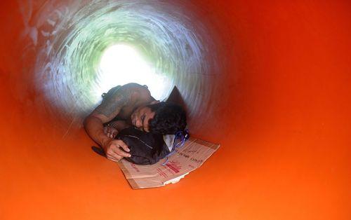 خواب یک کارگر فیلیپینی داخل یک لوله بزرگ پلاستیکی انتقال آب در یک شرکت اب در مانیل