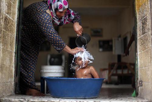 مادر فلسطینی در بیت لاحیا غزه در حال شستشوی پسرش پس از توفان شن