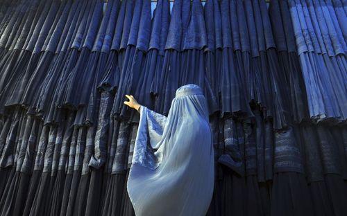 یک زن در حال خرید از یک فروشگاه عرضه چادر سنتی افغانی – برقع- در مزار شریف