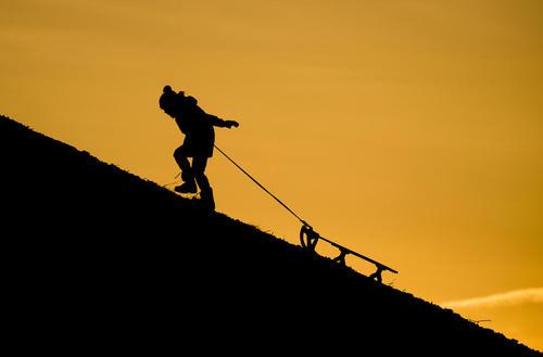 یک کودک آلمانی در حال بالا کشیدن سورتمه از دامنه کوهپایه- هانوفر