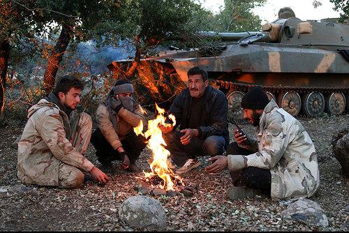 شورشیان مسلح در حال گرم شدن با آتش در استان قنیطره در منطقه جولان سوریه
