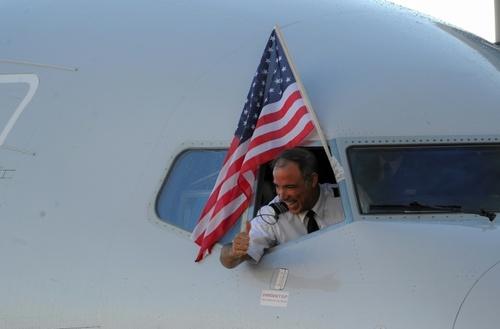 خلبان هواپیمای آمریکایی بعد از فرود در فرودگاه هاوانا پرچم آمریکا را از پنجره کابین خارج کرد و تکان داد. این نخستین پرواز مسافری میان شهر میامی امریکا و هاوانا کوبا بعد از 50 سال بود/ خبرگزاری فرانسه
