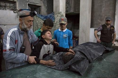 گریه یک نوجوان در شهر حلب سوریه بر سر جنازه اعضای خانواده اش