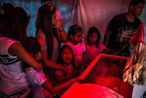 گریه دختر بچه 6 ساله فیلیپینی بر سر تابوت پدرش که به ظن ارتباط با باندهای قاچاق مواد مخدر در شهر مانیل به دست افراد ناشناس کشته شده است