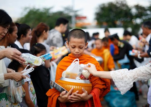 راهب نوجوان بودایی در حال جمع اوری اعانه از مردم – بانکوک