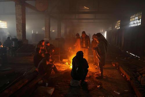 گرم شدن پناهجویان در داخل اردوگاهی در هوای سرد شهر بلگراد صربستان