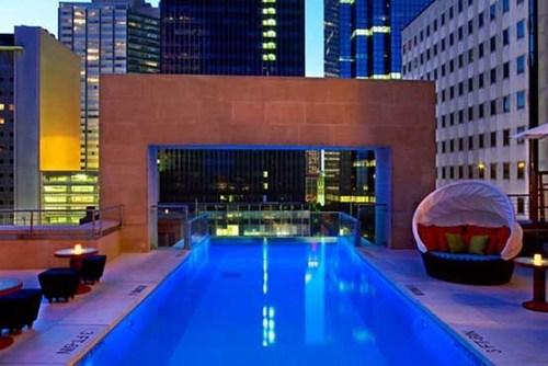 استخر هتل جول شهر دالاس ایالت تگزاس در میان آسمان خراش ها.