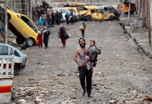 عکس رویترز از فرار مرد عراقی به همراه دخترش از قلمرو تحت اشغال داعش در شهر موصل به سمت نیروهای عراقی