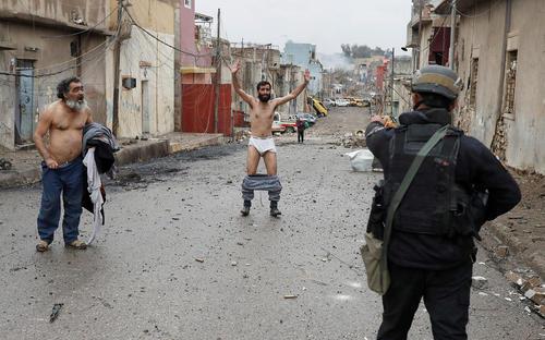 و این هم عکس دیگری از رویترز از فرار شهروندان عراقی . نیروی ارتش عراق به ظن تروریست بودن و اطمینان از نداشتن کمربند انتحاری از مرد عراقی خواسته تا لباس هایش را در آورد