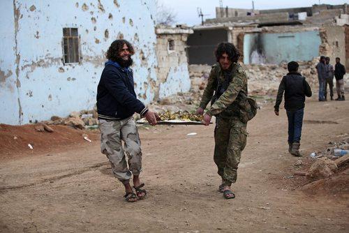 مخالفان مسلح حکومت سوریه در حال حمل سینی غذا به جشنی که به مناسبت بیرون کردن داعش از شهر الباب برگزار کرده اند