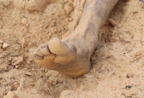 بیرون کشیدن بدن یک پناهجوی دفن شده در شن های سواحل لیبی