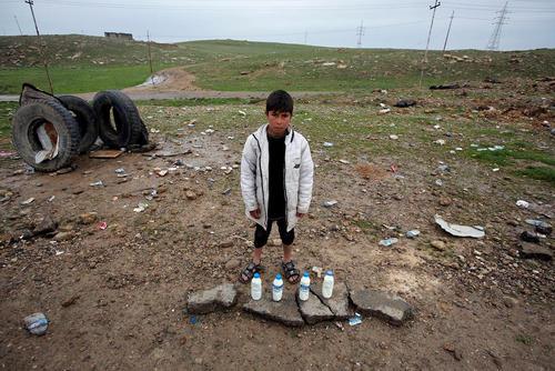 کودک عراقی در حال فروش شیر در کنار خیابان – موصل
