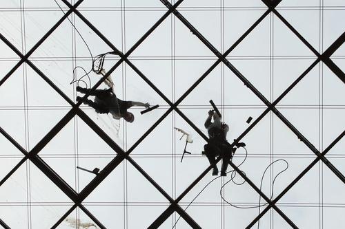 کارگران در حال تمیز کردن شیشه های نمای ساختمان مرکز تجارت جهانی در درسدن آلمان