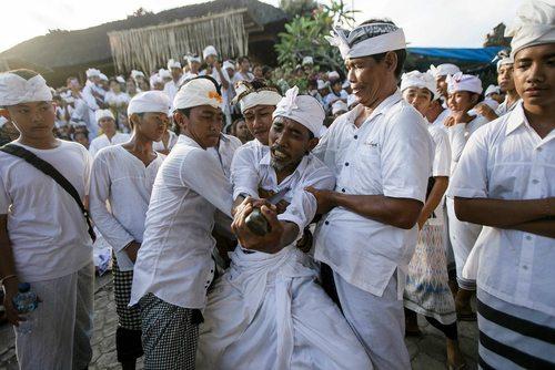 فرو کردن یک خنجر در حالت خلسه به بدن در یک مراسم آیینی در معبدی در دنپاسار اندونزی