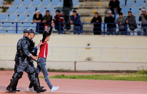 نیروهای امنیتی لبنان یکی از تماشاگران تیم ملی لبنان را به خارج از استادیوم منتقل می کنند