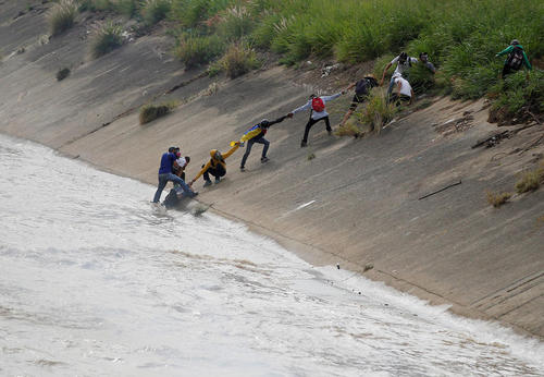 نجات یکه معترض پس از سقوط به رودخانه توسط سایر معترضان. این تظاهرات علیه نیکلاس مادورو رئیس جمهور ونزوئلا برگزار شده است.