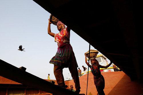 کارگران در حال جمع آوری ماسه های ساحلی از حاشیه رود بوریگانگا در شهر داکا بنگلادش