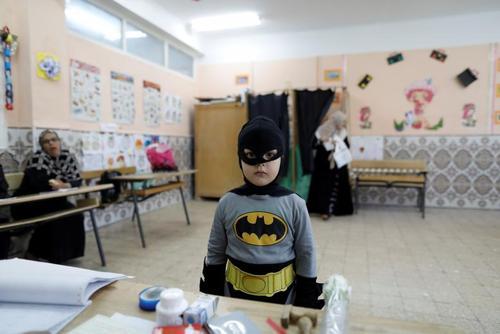 یک پسر بچه در لباس بتمن در یک حوزه رای گیری در انتخابات پارلمانی الجزایر