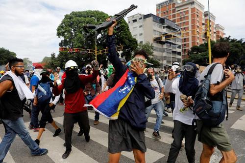گرفتن اسلحه پلیس از سوی معترضان مخالف در تظاهرات اعتراضی ضد دولتی در شهر کاراکاس ونزوئلا