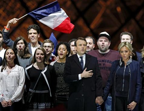 مکرون و همسرش در جمع هوادارانش پس از اعلام نتیجه اولیه آرا