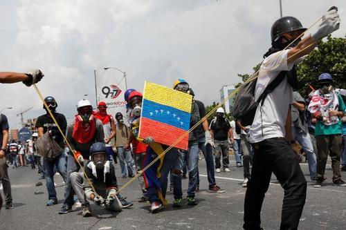 مخالفان حکومت ونزوئلا در حال پرتاب کوکتل مولوتف به سمت نیروهای پلیس در تظاهرات ضد دولتی - کاراکاس