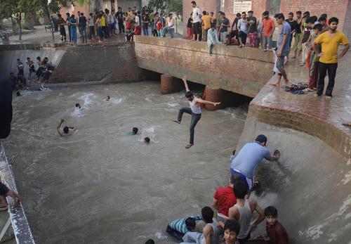 پریدن به داخل کانال آب برای خنک شدن در گرمای هوا- لاهور پاکستان