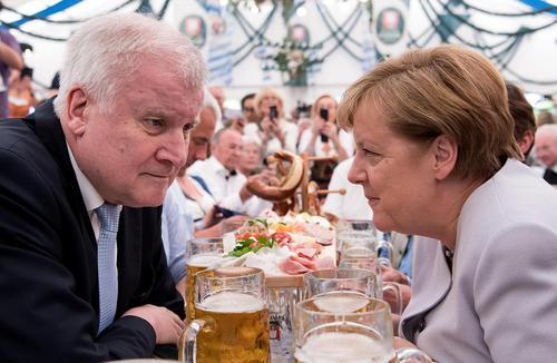 آنگلا مرکل صدر اعظم آلمان در حال گفتوگو با نخست وزیر ایالت باواریا آلمان در نخستین میتینگ انتخاباتی حزب حاکم آلمان در شهر مونیخ