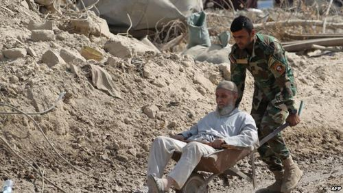 انتقال پیرمردی که توانایی فرار از محل درگیری ندارد توسط سرباز عراقی
