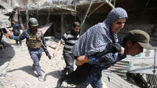 خارج کردن زنی که در محل درگیری گرفتار شده بود وتوان فرار نداشت توسط یک سرباز عراقی