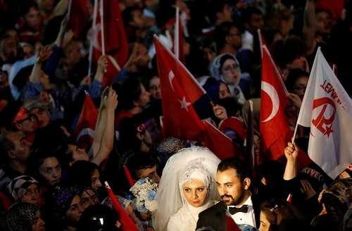 حضور یک عروس و داماد ترکیه ای در مراسم سالگرد شکست کودتای نافرجام ترکیه در مقابل ساختمان پارلمان در آنکارا