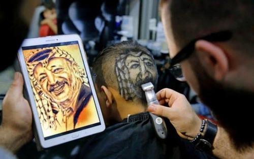یک سلمانی لبنانی در حال نقش کردن تصویر یاسر عرفات روی سر یک جوان فلسطینی – جنوب بیروت