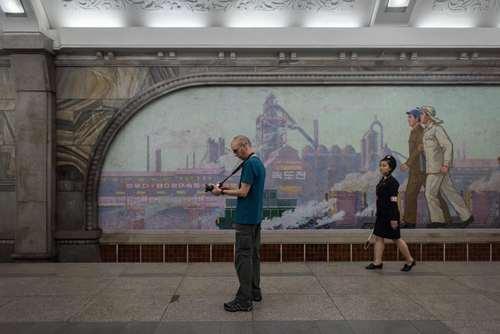 یک گردشگر غربی در حال گرفتن عکس از یک ایستگاه مترو در شهر پیونگ یانگ کره شمالی