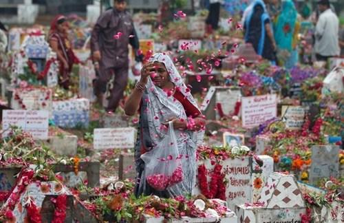 زنی هندو بر مزار عزیزانش در گورستانی در شهر احمد آباد هند در جشنواره آیینی دیواسو