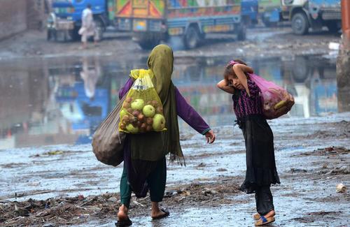دختران پناهجوی افغان در حال جمع آوری میوه های دورریز شده در بازاری در لاهور پاکستان