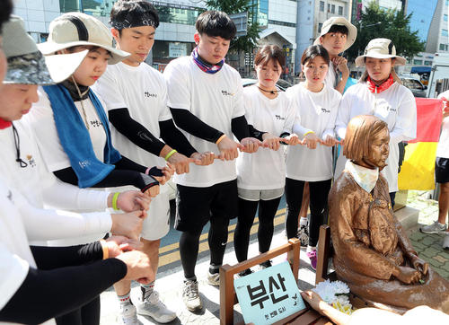 اعلام همبستگی گروهی از جوانان کره جنوبی با زنان کره ای قربانی تجاوز جنسی سربازان ژاپن در طی جنگ دوم جهانی در کنار یک مجسمه یادبود این بانوان در شهر بوسان