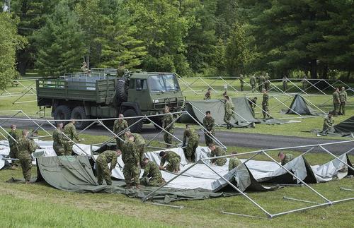 سربازان ارتش کانادا در حال ساخت چادر اسکان برای پناهجویان در مرز این کشور با آمریکا
