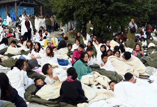 توریست ها در پارکینگی در شهر زلزله زده جیوژایگو چین - در استان سیچوان- در انتظار نیروهای امدای برای خروج از منطقه زلزله زده