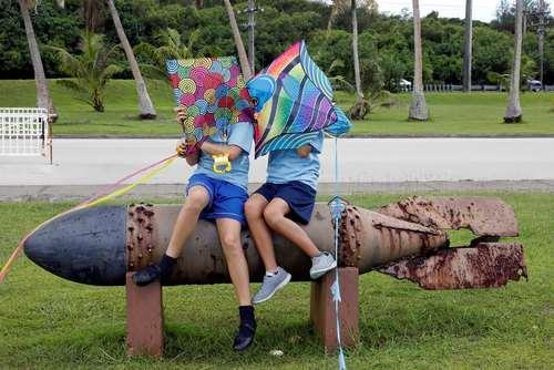 نشستن دانش آموزان روی یک بمب برجای مانده از دوران جنگ دوم جهانی در جزیره گوام