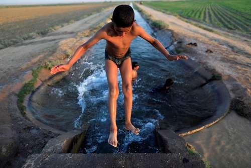 آب تنی کودکان در کانال آبی در شهر رقه سوریه