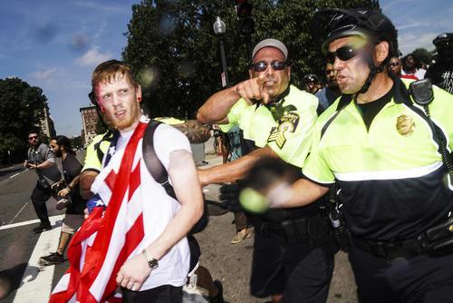 مشایعت یک مرد حامی نژادپرستان از سوی پلیس به بیرون از محل تجمع پس از پایان زودهنگام گردهمایی چند صد نفره آنها