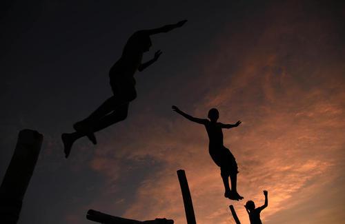 بازی نوجوانان هندی در غروب آفتاب در ساحل سنگام در کناره رود گنگ در شهر الله آباد
